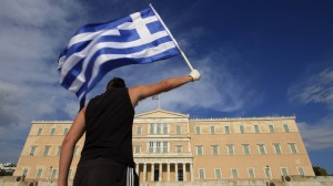 A protester raises Greek flag in front of the parliament during a rally against a new austerity package at Athens' Syntagma square