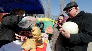 Customers choose chickens for sale at a food market, which operates once a week on Saturday, in the Russian southern city of Stavropol March 14, 2015. Russia's economy has slowed sharply in recent months as a collapse in oil prices and Western sanctions over the Ukraine crisis have dragged on growth.    REUTERS/Eduard Korniyenko (RUSSIA - Tags: BUSINESS SOCIETY FOOD) - RTR4TD12