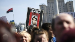 People hold a sign as they attend an anti-war rally at Independence Square in Kiev