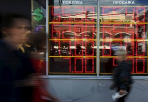 People walk past a board displaying currency exchange rates in Moscow, Russia, June 5, 2015. A slide in the rouble accelerated on June 4 after the Russian central bank said its policy of replenishing forex reserves would continue over several years until the reserves had reached pre-crisis levels. REUTERS/Sergei Karpukhin - RTX1F8ZN